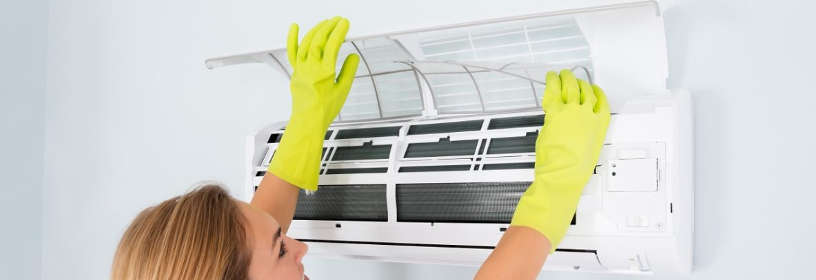 Woman checking her room air conditioner